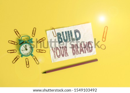 Handwriting text Build Your Brand. Concept meaning enhancing brand equity using advertising campaigns Metal alarm clock clips crushed sheet pencil rubber band colored background.