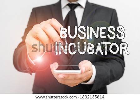 Handwriting text Business Incubator. Concept meaning company that helps new and startup companies to develop Male human wear formal work suit hold smart hi tech smartphone use one hand.