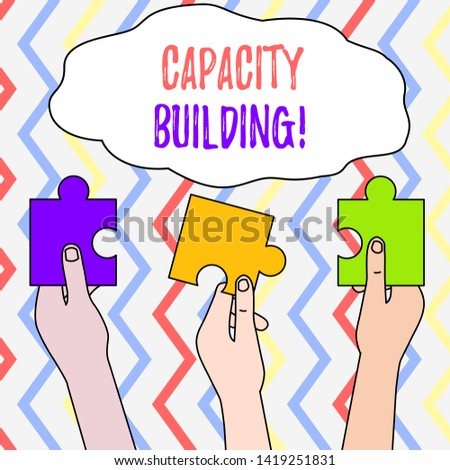 Handwriting text Capacity Building. Concept meaning Strengthen the abilities of individuals Workforce planning Three Colored Empty Jigsaw Puzzle Pieces Held in Different People Hands.