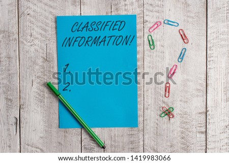 Handwriting text Classified Information. Concept meaning Sensitive Data Top Secret Unauthorized Disclosure Pastel colour note paper placed next to stationary above the wooden table.