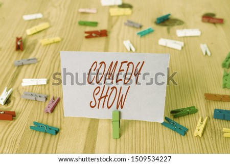 Handwriting text Comedy Show. Concept meaning Funny program Humorous Amusing medium of Entertainment Colored clothespin papers empty reminder wooden floor background office. #1509534227