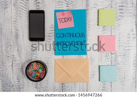 Handwriting text Continuous Improvement. Concept meaning ongoing effort to improve products or processes Envelope letter smartphone note clips notepads wooden vintage background.