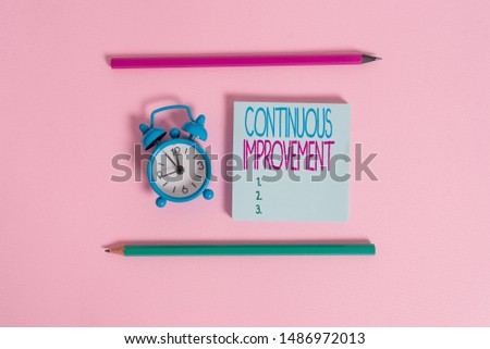 Handwriting text Continuous Improvement. Concept meaning ongoing effort to improve products or processes Metal vintage alarm clock wakeup blank notepad markers colored background.