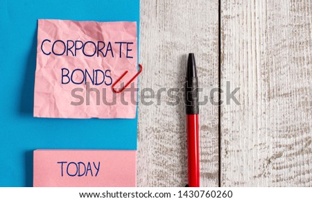 Handwriting text Corporate Bonds. Concept meaning corporation to raise financing for variety of reasons Wrinkle paper and cardboard plus stationary placed above wooden background. #1430760260