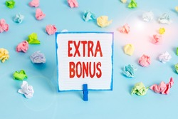 Handwriting text Extra Bonus. Concept meaning an extra amount of money that is added to someone s is pay Colored crumpled papers empty reminder blue floor background clothespin.