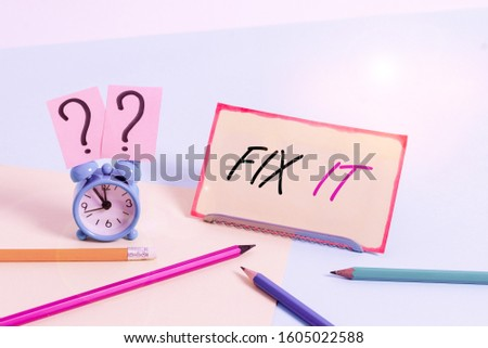 Handwriting text Fix It. Concept meaning Fasten something securely in a particular place or position To repair Mini size alarm clock beside stationary placed tilted on pastel backdrop.
