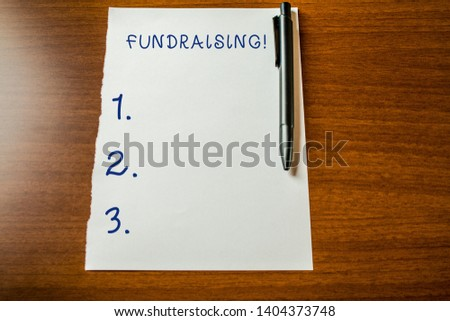 Handwriting text Fundraising. Concept meaning seeking to generate financial support for charity or cause Upper view blank stationary paper lying wooden table pen. Writing essay. #1404373748
