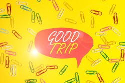 Handwriting text Good Trip. Concept meaning A journey or voyage,run by boat,train,bus,or any kind of vehicle Flat lay above empty paper with copy space and colored paper clips.