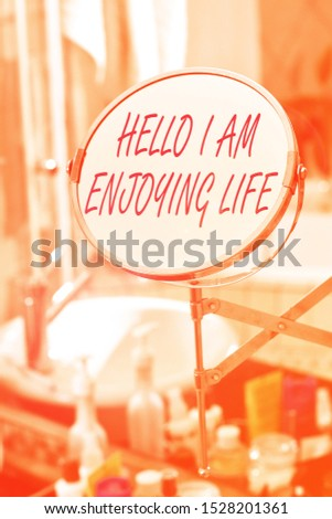 Handwriting text Hello I Am Enjoying Life. Concept meaning Happy relaxed lifestyle Enjoy simple things Round shape mirror and toiletries placed next to sink in a modern bathroom. #1528201361