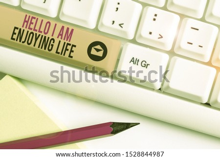 Handwriting text Hello I Am Enjoying Life. Concept meaning Happy relaxed lifestyle Enjoy simple things White pc keyboard with empty note paper above white background key copy space. #1528844987