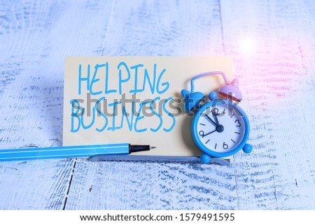 Handwriting text Helping Business. Concept meaning improving some measure of an enterprise s is success Mini blue alarm clock stand tilted above buffer wire in front of notepaper.