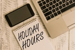 Handwriting text Holiday Hours. Concept meaning Schedule 24 or7 Half Day Today Last Minute Late Closing Metallic laptop blank ruled notepad smartphone lying old wooden table.