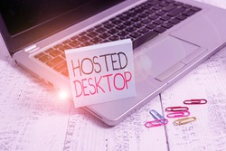 Handwriting text Hosted Desktop. Concept meaning product set within the larger cloudcomputing sphere Trendy metallic laptop blank sticky pad clips lying wooden vintage table.