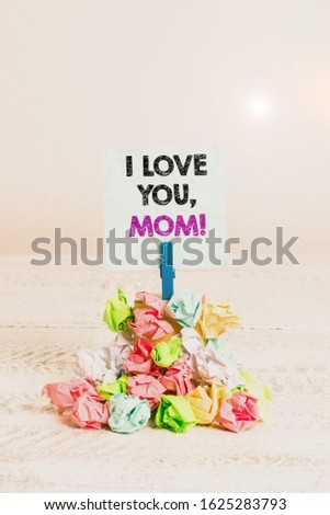 Handwriting text I Love You, Mom. Concept meaning Loving message emotional feelings affection warm declaration Reminder pile colored crumpled paper clothespin reminder white wooden space.