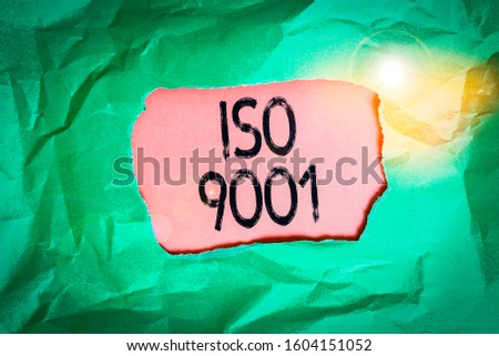 Handwriting text Iso 9001. Concept meaning designed help organizations to ensure meet the needs of customers Green crumpled ripped colored paper sheet centre torn colorful background.