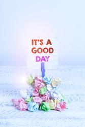 Handwriting text It s is A Good Day. Concept meaning Happy time great vibes perfect to enjoy life beautiful Reminder pile colored crumpled paper clothespin reminder white wooden space.