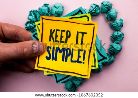 Handwriting text Keep It Simple Motivational Call. Concept meaning Simplify Things Easy Clear Concise Ideas written on Sticky Note Paper Holding by man plain background on Heart Paper Balls.