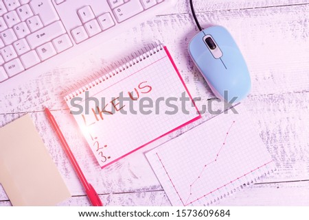 Handwriting text Like Us. Concept meaning Asking to follow on social media Feel attraction or pleasure Writing equipments and computer stuffs placed above classic wooden table. #1573609684