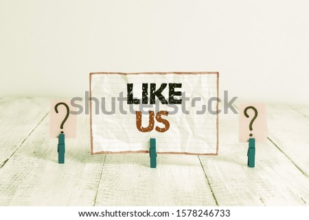 Handwriting text Like Us. Concept meaning Asking to follow on social media Feel attraction or pleasure Scribbled and crumbling sheet with paper clips placed on the wooden table. #1578246733