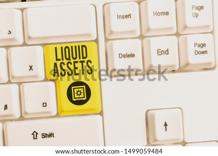 Handwriting text Liquid Assets. Concept meaning Cash and Bank Balances Market Liquidity Deferred Stock White pc keyboard with empty note paper above white background key copy space. #1499059484