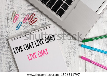 Handwriting text Live Chat Live Chat Live Chat. Concept meaning talking with showing friends relatives online Slim metallic laptop blank spiral notepad pens clips lying wooden table.