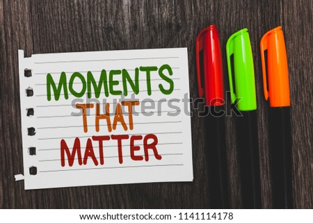 Handwriting text Moments That Matter. Concept meaning Meaningful positive happy memorable important times Colorful words with white page red green orange pen on blackish wooden desk. #1141114178