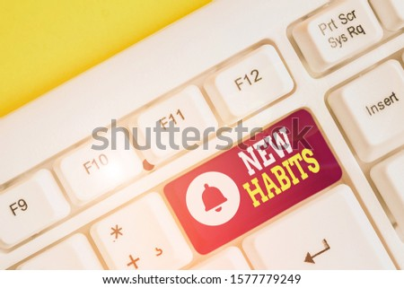 Handwriting text New Habits. Concept meaning change the routine of behavior that is repeated regularly White pc keyboard with empty note paper above white background key copy space.