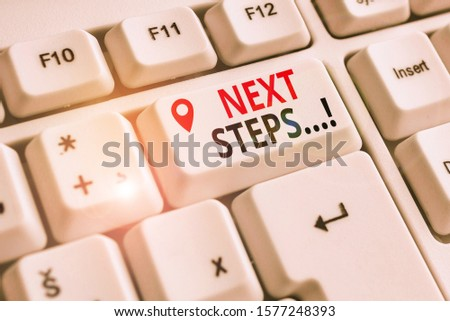 Handwriting text Next Steps. Concept meaning something you do after you have finished doing first one White pc keyboard with empty note paper above white background key copy space. #1577248393