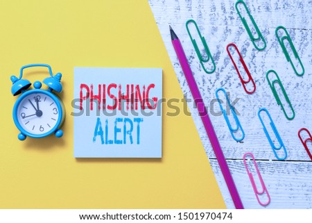 Handwriting text Phishing Alert. Concept meaning aware to fraudulent attempt to obtain sensitive information Notepad marker pen colored paper sheet clips alarm clock wooden background.