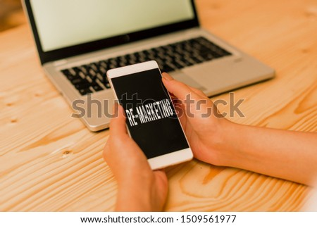 Handwriting text Re Marketing. Concept meaning Strategy to reach potential customers in your website woman laptop computer smartphone mug office supplies technological devices.