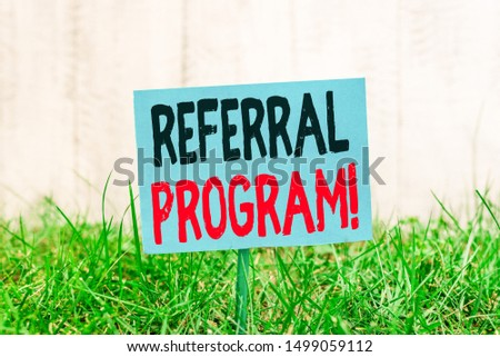 Handwriting text Referral Program. Concept meaning internal recruitment method employed by organizations Plain empty paper attached to a stick and placed in the green grassy land. #1499059112