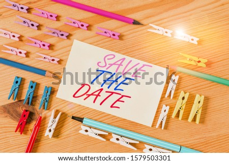 Handwriting text Save The Date. Concept meaning Systematized events Scheduled activity Recorded Filed Colored clothespin papers empty reminder wooden floor background office.
