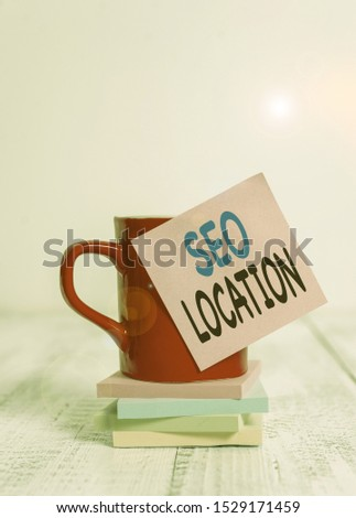 Handwriting text Seo Location. Concept meaning process to optimize pages on your site to show for organic Coffee cup blank sticky note stacked note pads retro retro wooden table.