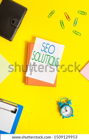 Handwriting text Seo Solutions. Concept meaning Search Engine Result Page Increase Visitors by Rankings Paper clips with blank papers for text messages. #1509129953