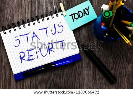 Handwriting text Status Report. Concept meaning Update Summary of situations as of a period of time Open notebook clothespin holding reminder cup markers wooden background. #1189066492