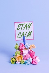 Handwriting text Stay Calm. Concept meaning Maintain in a state of motion smoothly even under pressure Reminder pile colored crumpled paper clothespin reminder blue background.
