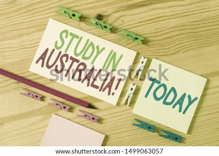 Handwriting text Study In Australia. Concept meaning going into foreign country order complete your studies Colored clothespin papers empty reminder wooden floor background office.