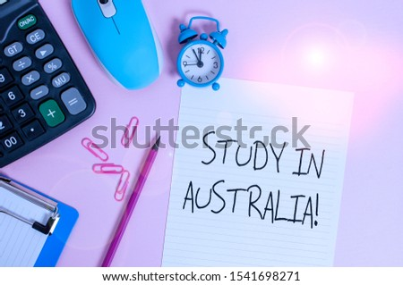 Handwriting text Study In Australia. Concept meaning going into foreign country order complete your studies Calculator clips clock clipboard mouse sheet pencil colored background.