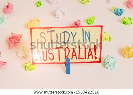 Handwriting text Study In Australia. Concept meaning going into foreign country order complete your studies Colored crumpled papers empty reminder white floor background clothespin.