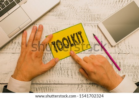 Handwriting text Toolkit. Concept meaning set of tools kept in a bag or box and used for a particular purpose Hand hold note paper near writing equipment and modern smartphone device. #1541702324