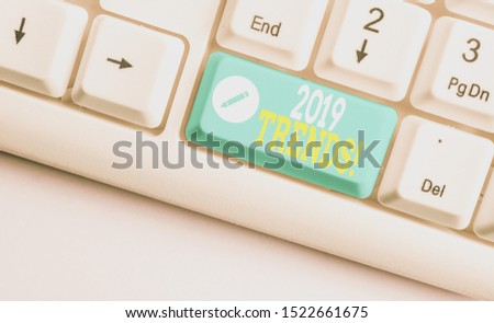 Handwriting text 2019 Trends. Concept meaning general direction in which something is developing or changing White pc keyboard with empty note paper above white background key copy space.