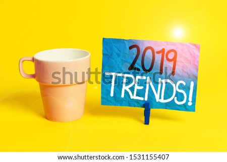 Handwriting text 2019 Trends. Concept meaning general direction in which something is developing or changing Cup empty paper blue clothespin rectangle shaped reminder yellow office.