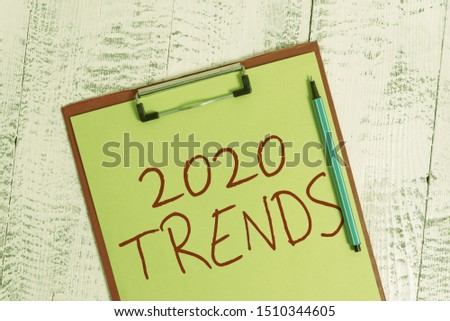 Handwriting text 2020 Trends. Concept meaning things that is famous for short period of time in current year Colored clipboard blank paper sheet marker old wooden vintage background.
