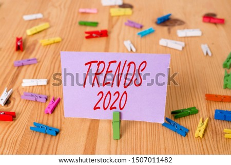 Handwriting text Trends 2020. Concept meaning Upcoming year prevailing tendency Widely Discussed Online Colored clothespin papers empty reminder wooden floor background office.