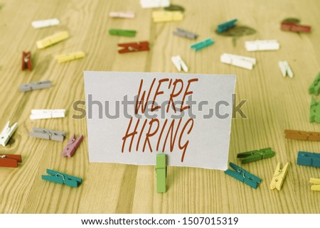 Handwriting text We Re Hiring. Concept meaning Advertising Employment Workforce Placement New Job Colored clothespin papers empty reminder wooden floor background office.