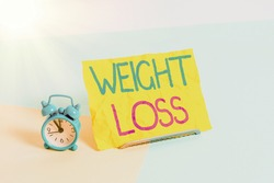 Handwriting text Weight Loss. Concept meaning the fact of a demonstratings is or an animals is body weight becoming less Mini size alarm clock beside a Paper sheet placed tilted on pastel backdrop.