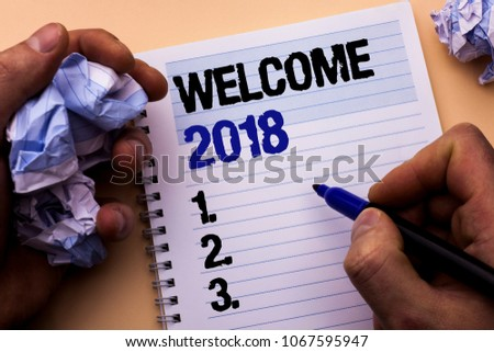Handwriting text Welcome 2018. Concept meaning Celebration New Celebrate Future Wishes Gratifying Wish written by Man on Notebook Book Holding Marker on the plain background. #1067595947