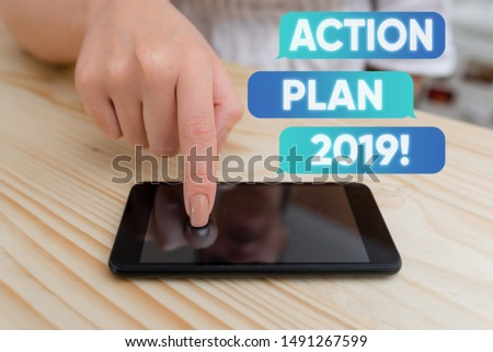 Handwriting text writing Action Plan 2019. Concept meaning proposed strategy or course of actions for current year woman using smartphone office supplies technological devices inside home.