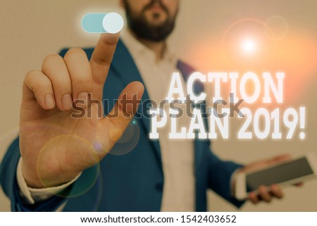 Handwriting text writing Action Plan 2019. Concept meaning proposed strategy or course of actions for current year Male human wear formal work suit presenting presentation using smart device. #1542403652