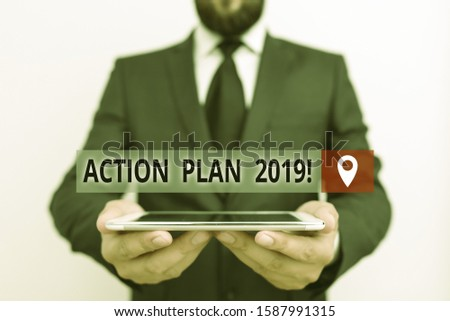 Handwriting text writing Action Plan 2019. Concept meaning proposed strategy or course of actions for current year Male human wear formal work suit hold smart hi tech smartphone use hands.